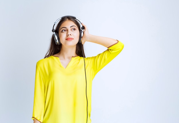 Girl with headphones staying calm and enjoying the music.