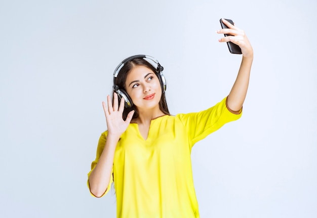ヘッドフォンを持った女の子が自分撮りをしたり、ビデオ通話をしたりしています。