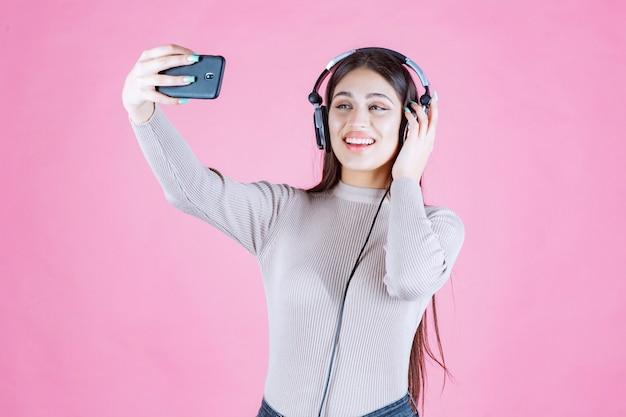 그녀의 selfie를 복용하는 헤드폰 소녀