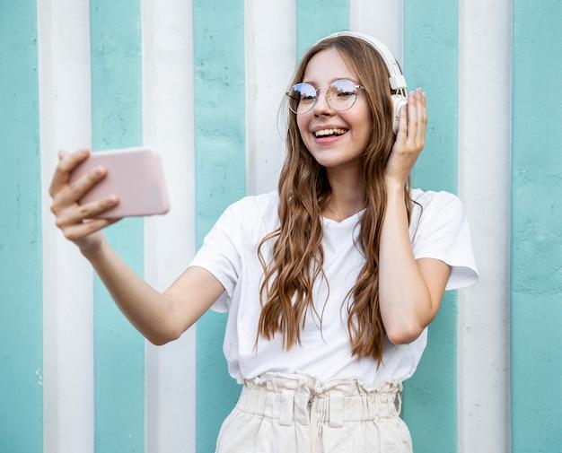 Selfieを取ってヘッドフォンを持つ少女