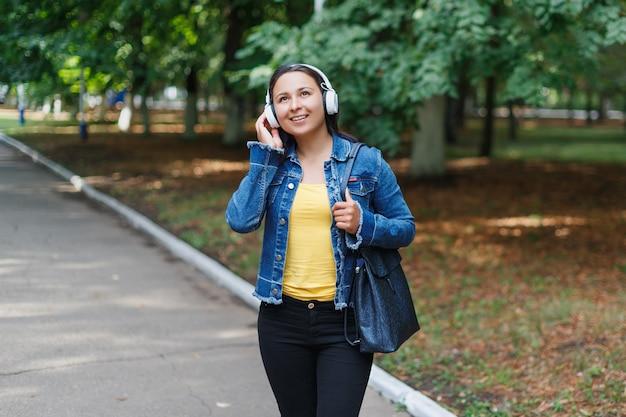 晴れた日に公園を歩き、音楽を聴いているヘッドフォンを持つ少女