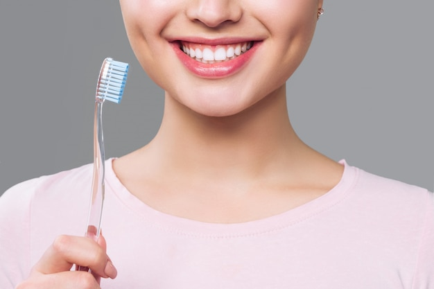 Girl with healthy white teeth holds a toothbrush and smiles. oral hygiene concept