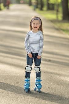 Девушка с шлемом и коньками в аллее