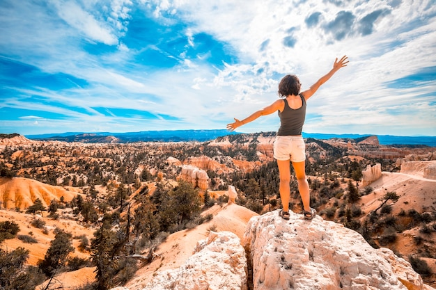 A girl with her arms outstretched enjoying the views from the sunrise point in bryce national park. utah, united states