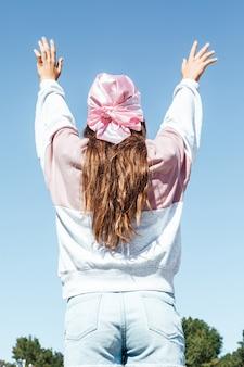 彼女の背中を持つ少女はピンkheadscarfで向きを変えた。空を背景にした国際乳がんデー。
