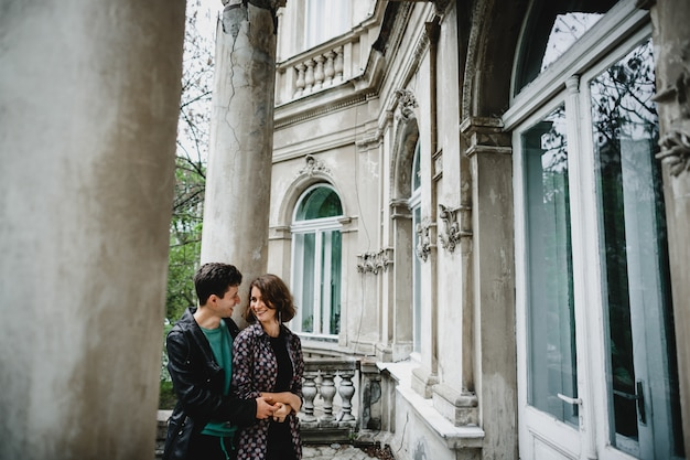 Girl with her boyfriend stand near old building and smile to each other
