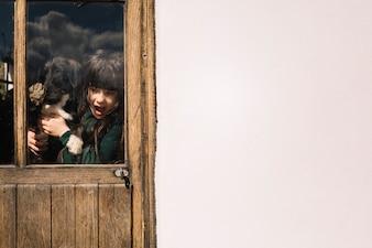 Girl with her dog seen through transparent glass door