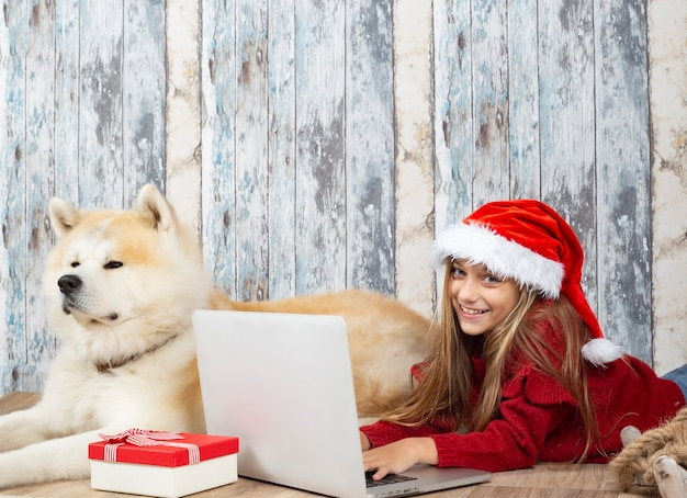 クリスマスにコンピューターを使用して彼女の犬と女の子