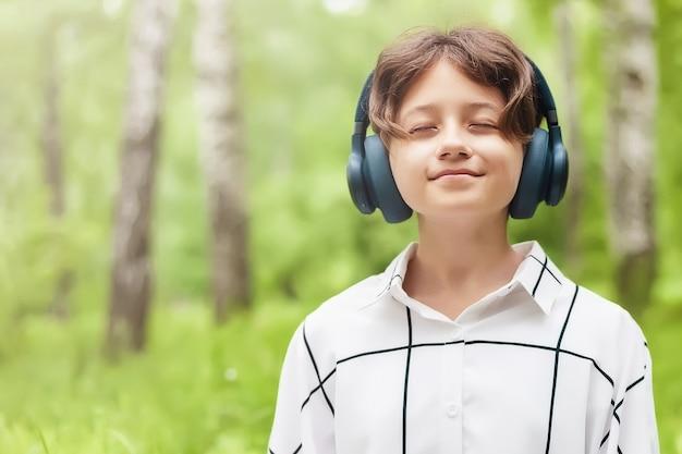 目を閉じて夏の屋外でヘッドフォンで音楽を聴く女の子