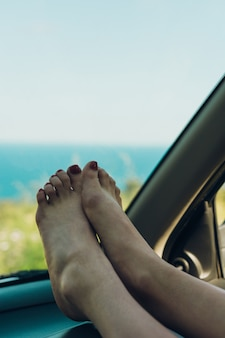 Girl with her feet out of the window of the car sunbathing on a summer afternoon,