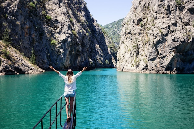 Girl with her hands up stands on bow of ship in waters of green canyon