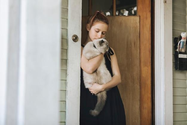 Девушка со своим домашним котом стоит у двери во время изоляции от коронавируса