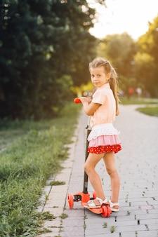 공원에 서있는 그녀의 푸시 스쿠터와 소녀