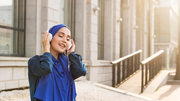 Girl with hijab listening to music through headphones