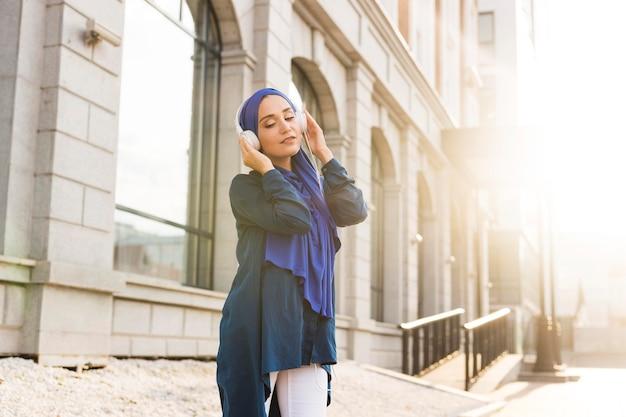 屋外のヘッドフォンを通して音楽を聴くヒジャーブを持つ少女