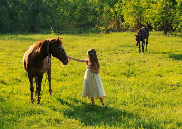 Girl with a horse in summer