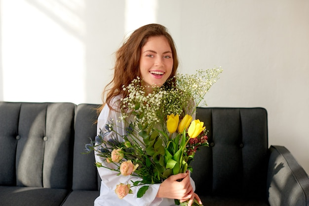 Girl with a huge bouquet of spring wildflowers in her hands rejoices and laughs, sitting on couch at home