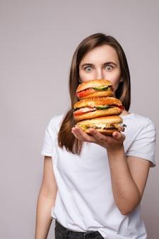 手に巨大なハンバーガーを持つ少女。ショックを受けた、またはカメラに驚いた彼女の手に巨大なハンバーガーを持っている白いtシャツの若いブルネットの女性のスタジオポートレート。