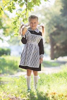 秋の路上に立っている制服の手でアイスクリームを持つ少女