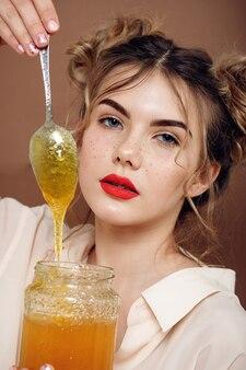 꿀 항아리와 소녀입니다. 건강 식품 개념, 다이어트, 디저트. 아름다운 소녀 미소는 꿀이 든 은수저를 들고 있다