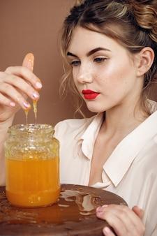꿀 항아리와 소녀입니다. 건강 식품 개념, 다이어트, 디저트. 아름다운 소녀가 웃고 항아리에서 손으로 꿀을 만진다