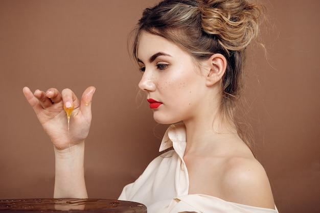 꿀 항아리와 소녀입니다. 건강 식품 개념, 다이어트, 디저트. 아름다운 소녀는 미소를 짓고 탁자 위에 손으로 꿀을 만진다
