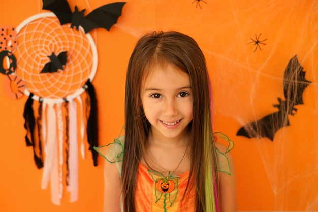 ハロウィーンの装飾が施されたオレンジ色のスタジオの背景に分離されたうれしそうな輝く笑顔の女の子