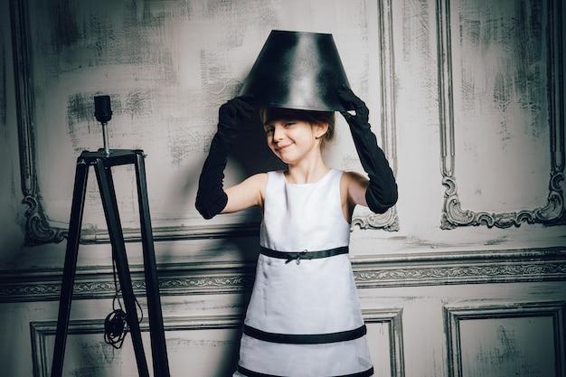 ヴィンテージのドレスにランプシェードの帽子の少女。エレガントで華やかなドレスと手袋をした子供。レトロな女の子、ファッションモデル、美容。レトロ、理髪店、化粧、ピンナップ。ファッション、ピンナップスタイル、子供時代。