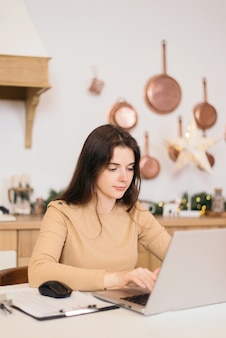 Девушка с ноутбуком делает домашнее задание на яркой кухне с рождественскими украшениями.