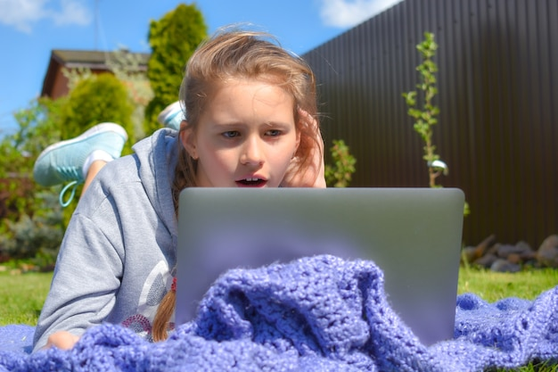 Girl with a laptop on the grass. online distance learning outdoor.