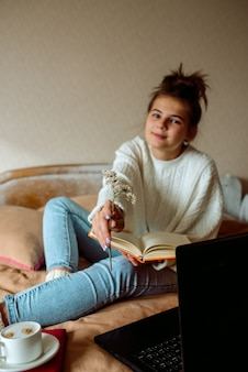 Girl with a laptop in her hands sitting on the bed.