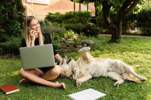 Девушка с ноутбуком, играя с собакой лабрадор в парке