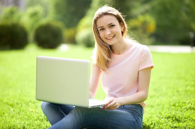 草の上に座って笑っているラップトップを持つ少女