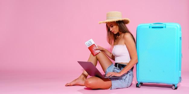 Девушка с ноутбуком, билетами, деньгами и паспортом собирается в путешествие, сидя возле чемодана в шортах ...