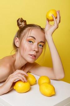 밝은 화장으로 노란색 벽에 레몬 소녀. 여름 분위기 프리미엄 사진