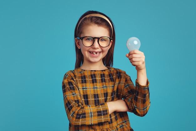 Девушка с лампочкой улыбается, имея блестящую идею на синей стене