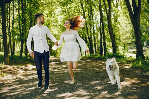 Girl with light hair dressed in white dress is playing along with her dog and boyfriend