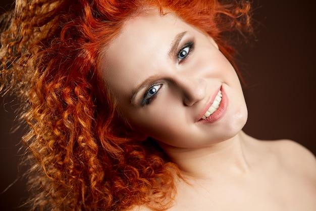 長く光沢のあるウェーブのかかった赤い髪の少女。巻き毛のヘアスタイルを持つ美しいモデル