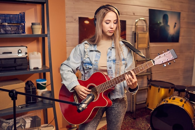 スタジオでエレキギターを弾く長いブロンドの髪の少女
