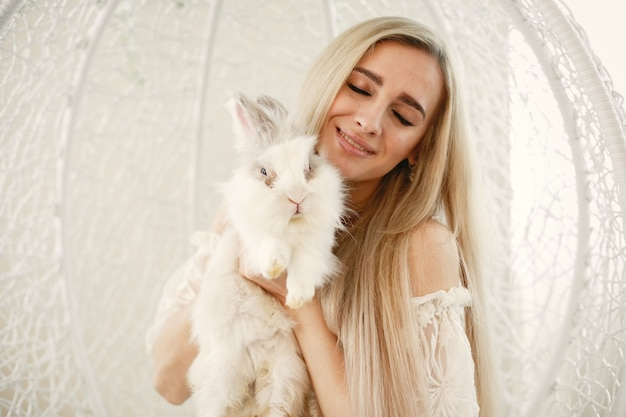 Girl with long blond hair with a white rabbit in her arms.