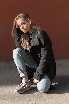 Girl with long blonde hair in black coat, jeans tucked up below and sneakers sits on pavement.