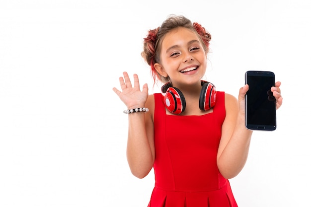 Girl with long blonde hair, dyed tips pink, stuffed in two tufts, in red dress, with red headphones, bracelet, standing and holding phone in hand and smiles