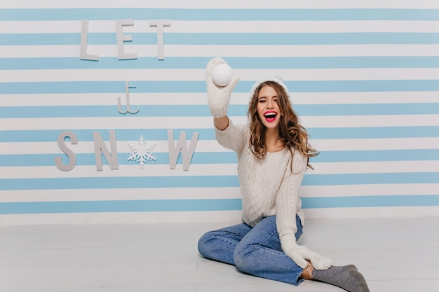 Girl with long curly hair and bright lipstick is jokingly posing, throwing snowball towards
