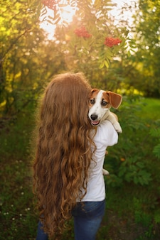A girl with long curly hair is standing with her back and holding a puppy in her arms.