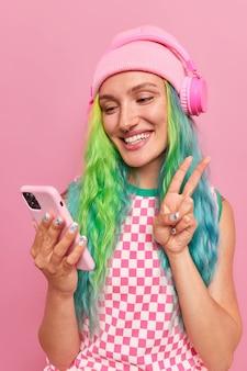 長い染めた髪の少女が友人に挨拶し、ビデオ通話を行います平和のジェスチャーがモバイルアプリを介して会話しますアプリレコードブログライブストリームとスタイリッシュな服を着たアプリケーション
