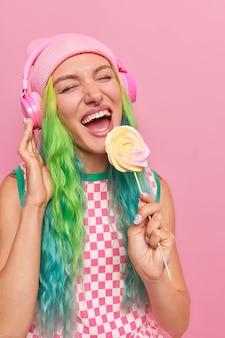 長い染めた髪の少女はスティックにおいしいキャンディーを保持しますヘッドフォンでお気に入りの曲を聴きますカジュアルなドレスとピンクで隔離の帽子を着ています
