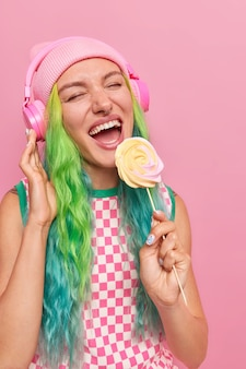 Girl with long dyed hair holds delicious candy on stick listens favorite song in headphones wears casual dress and hat isolated on pink