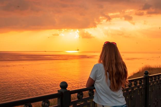 Девушка с длинными волосами на берегу моря на закате в оранжевом, летние каникулы, стрекозы летают против неба