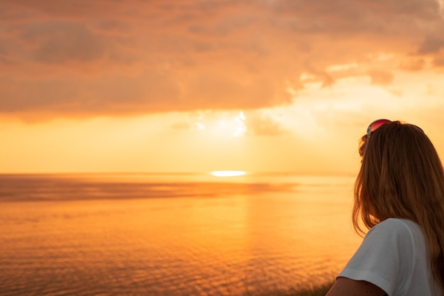 Девушка с длинными волосами у моря на закате, летние каникулы, прощание с морем