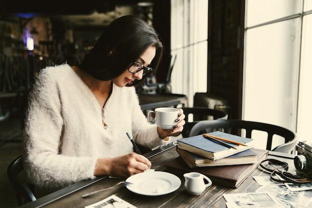 長い髪の女の子はカフェのテーブルでコーヒーを飲み、いくつかの音符を作る